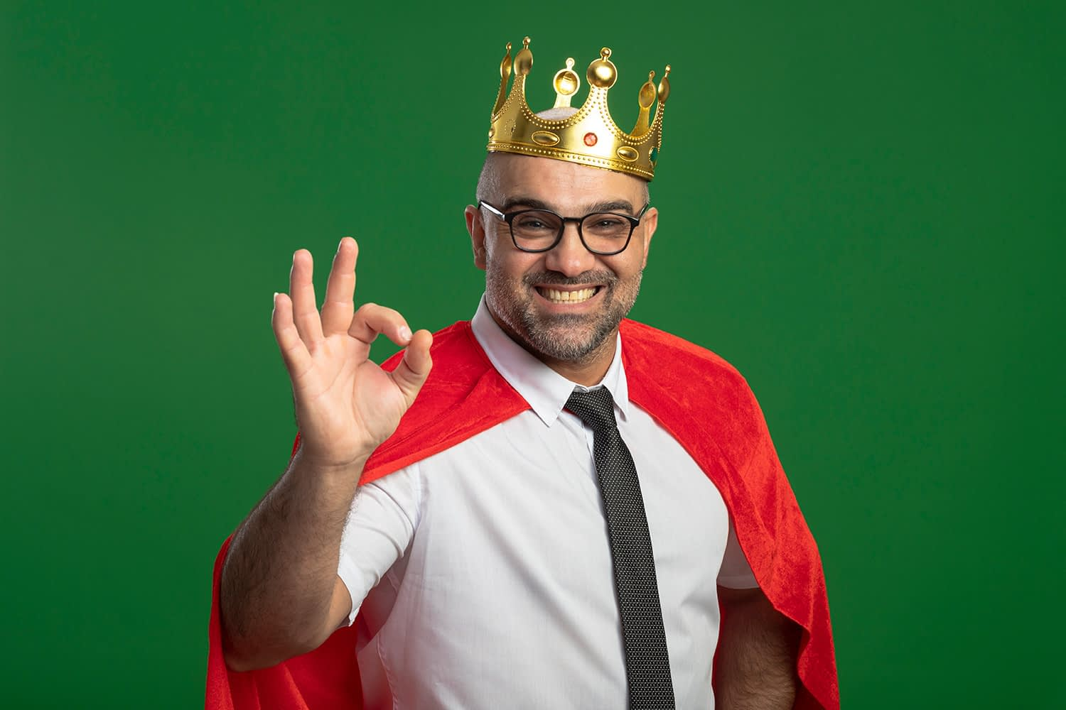 Super hero businessman in red cape and glasses wearing crown looking at front smiling cheerfully showing ok sign standing green white wall.