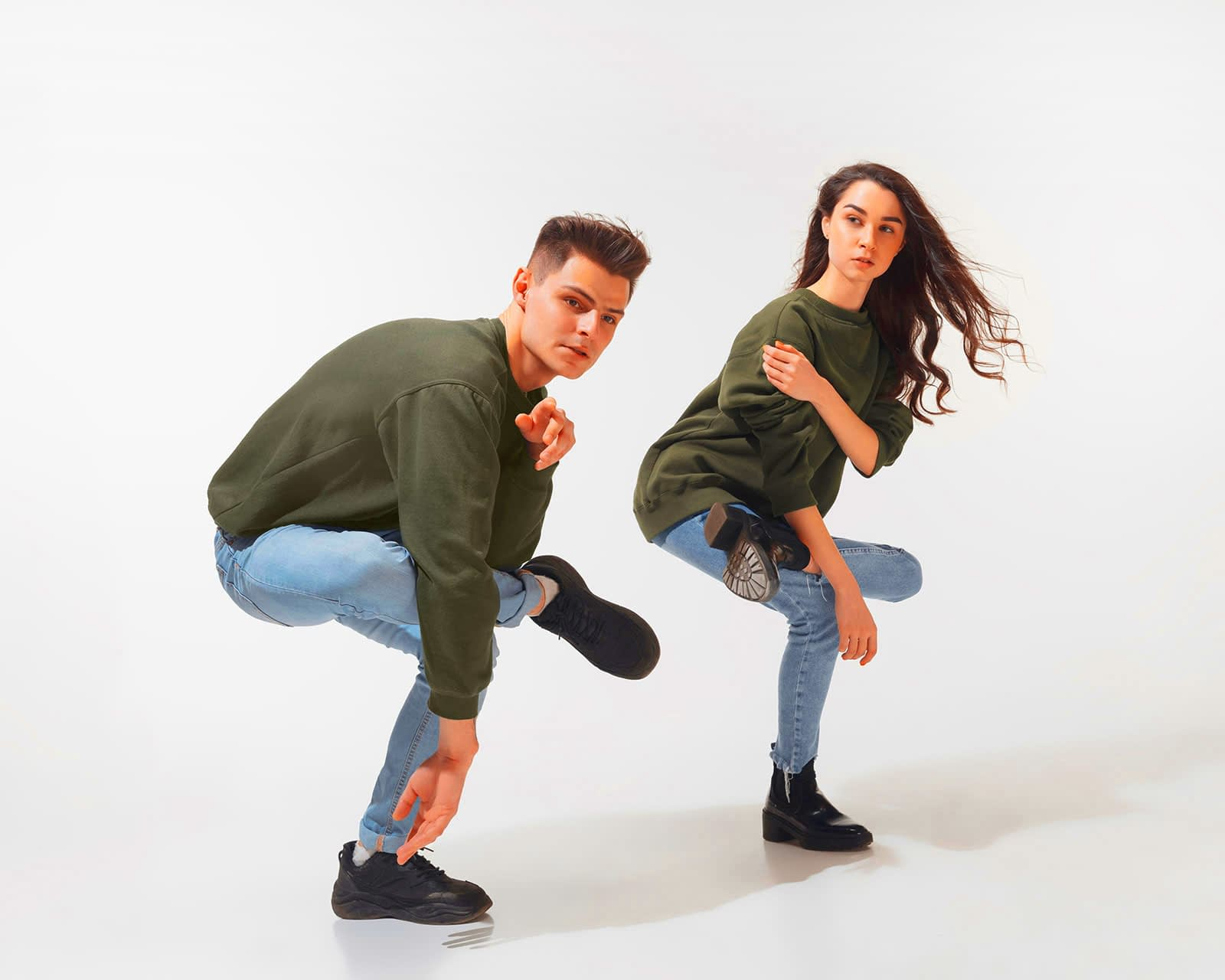 Trendy fashionable couple posing together in studio.