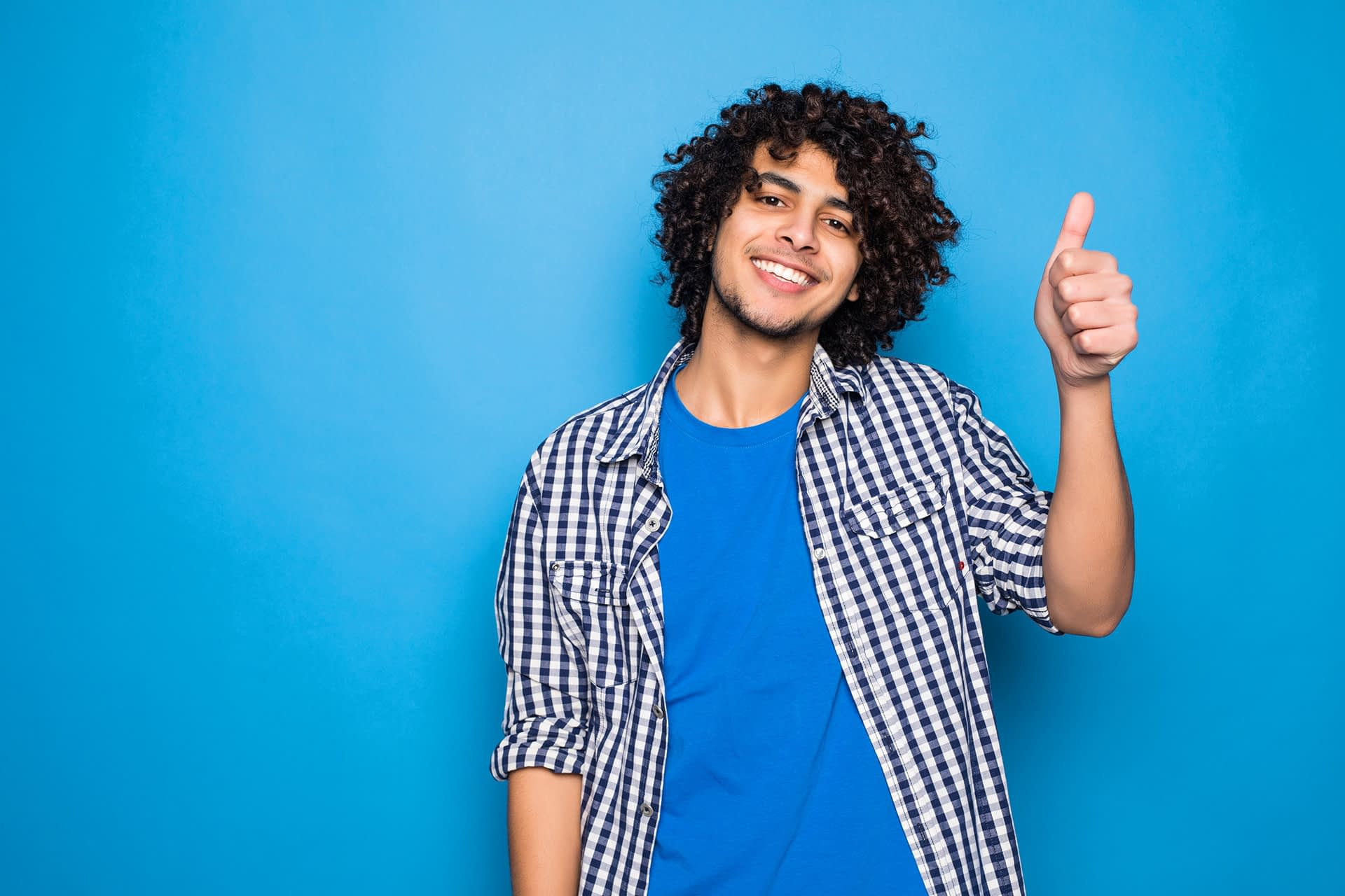 Young curly man with thumbs up standing in front of isolated blue wall.