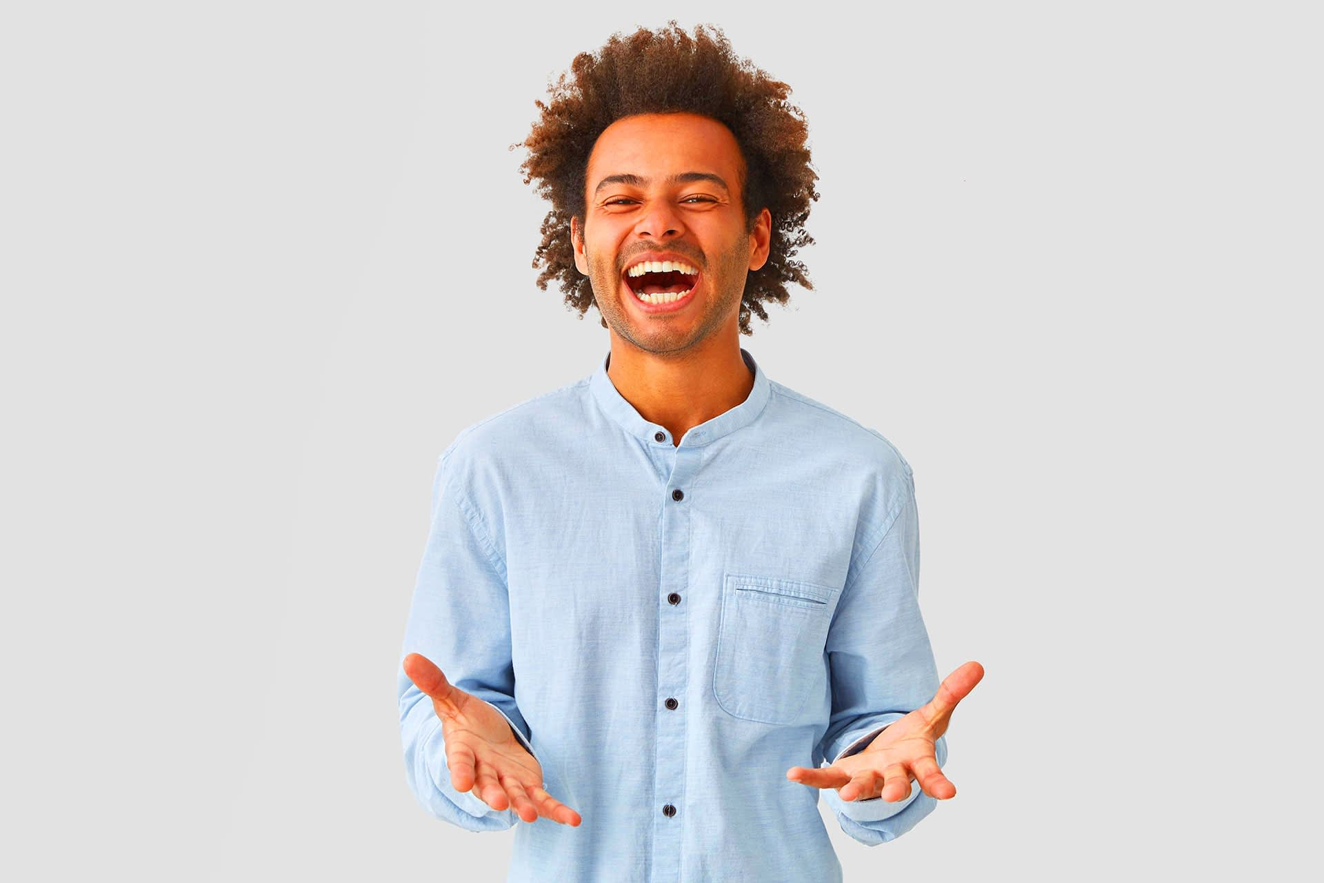 Overjoyed attractive man dressed in elegant shirt opens mouth widely, laughs joyfully, expresses positivity.