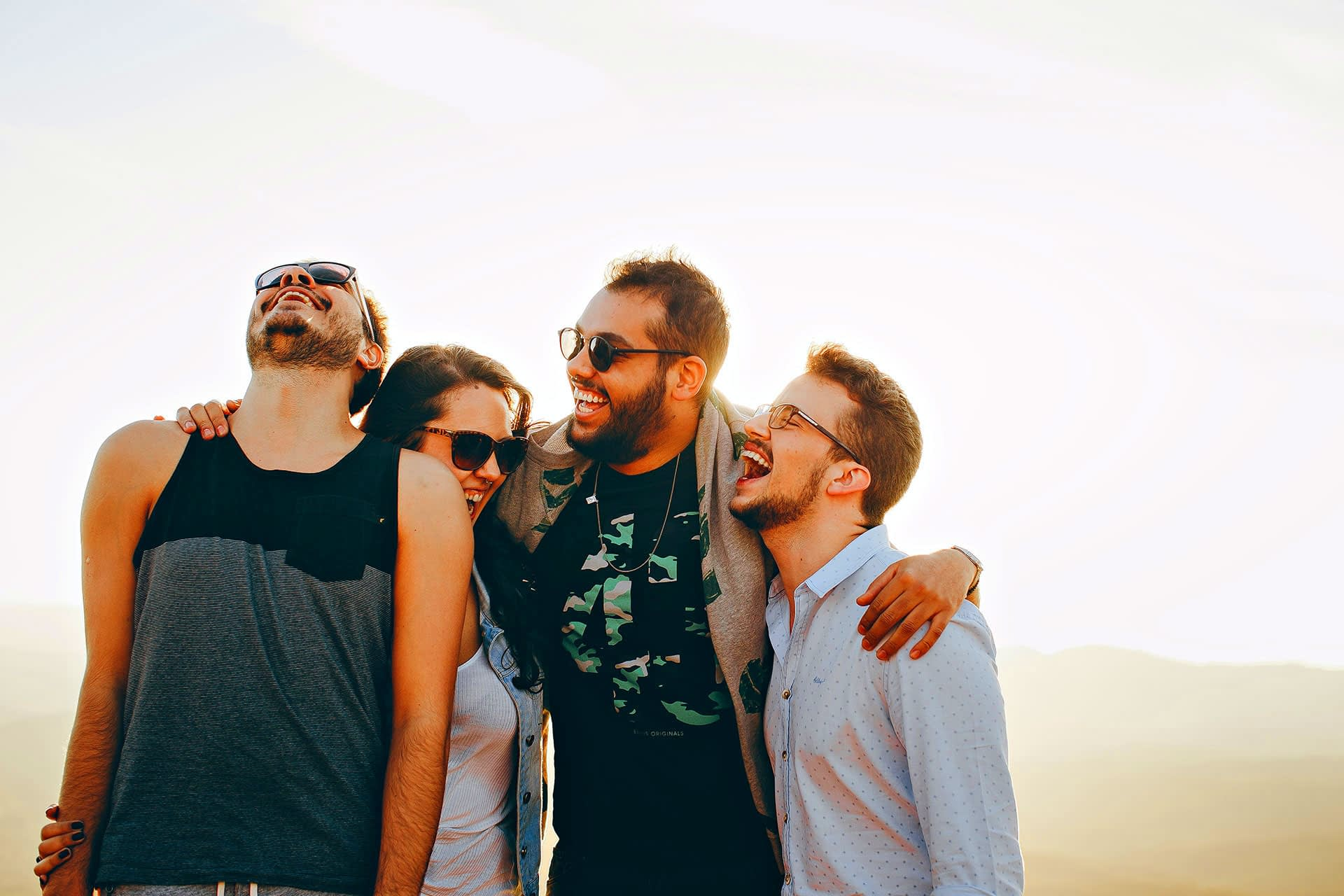 A group of young people are laughing outdoor.