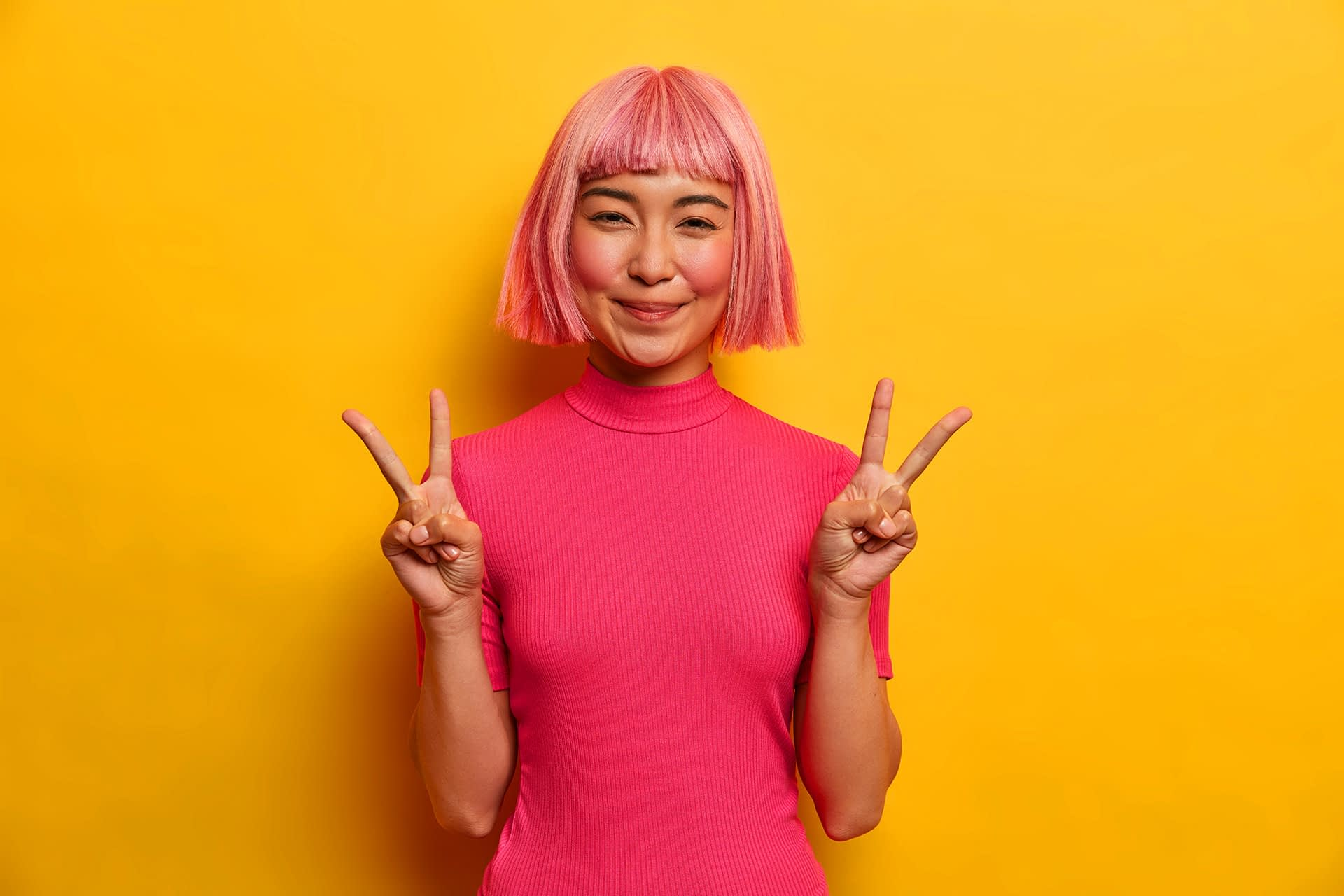 A happy Asian girl who makes a peace sign.