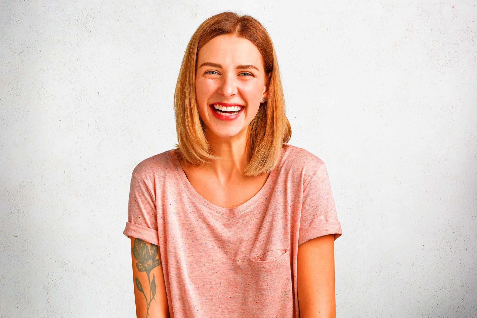 Positive adorable woman with bobbed hairdo, smiles gently at camera, has tattooed arm and healthy skin, being in good mood.