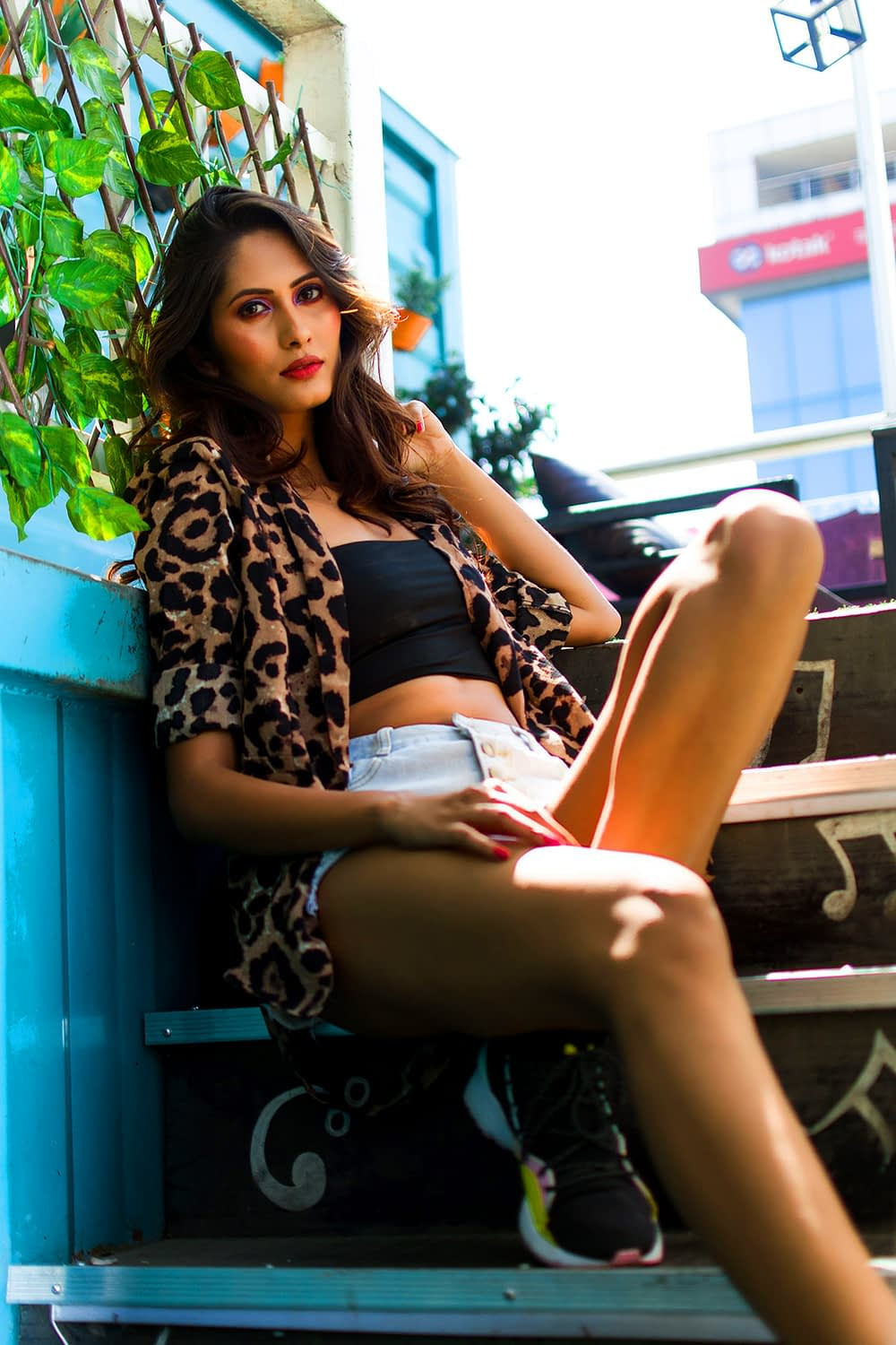 A young woman wearing leopard print and sitting on stairs.