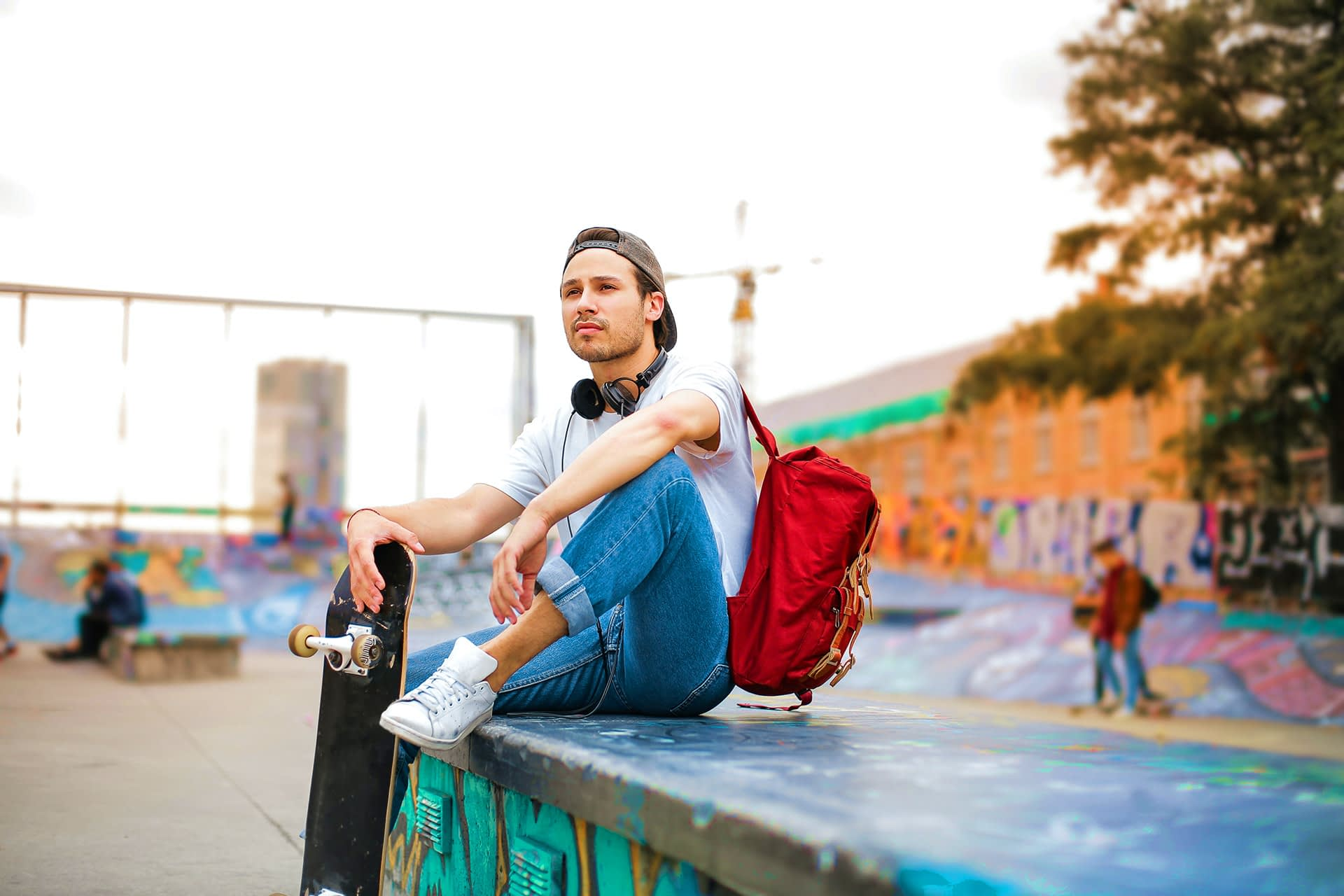 A young male skater with backpack sitting on ramp.