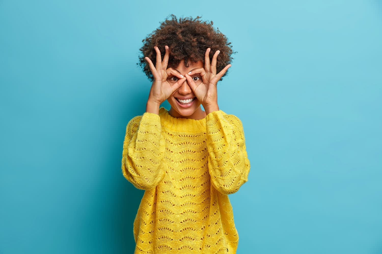 Playful curly haired woman in a yellow sweater making finger glasses with a smile.