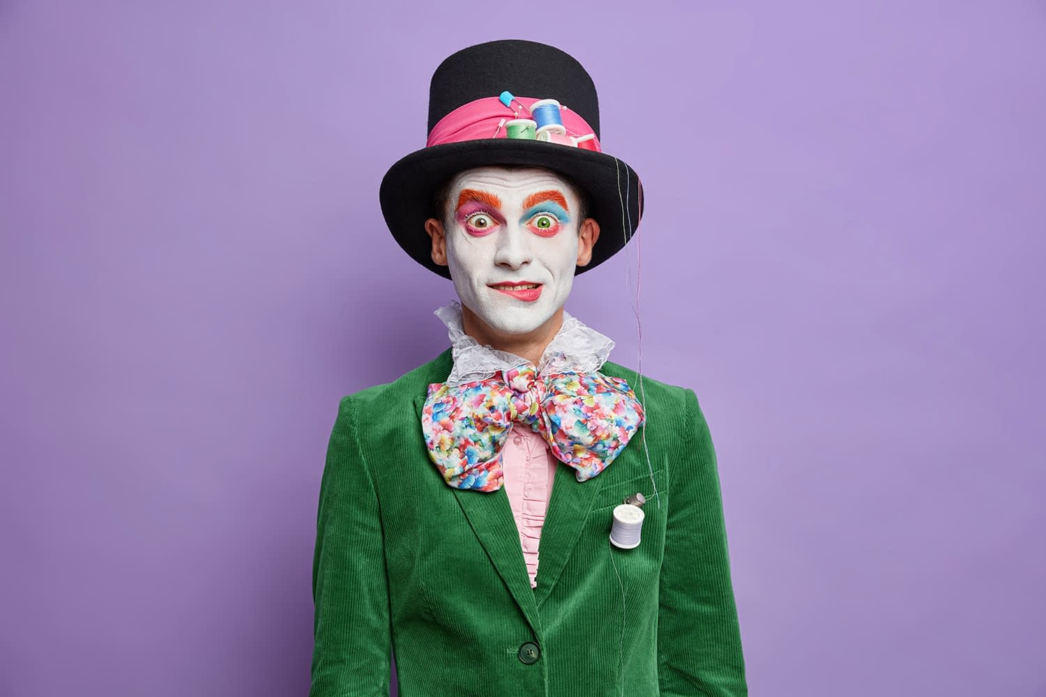 Surprised parade festival participant has image of hatter from wonderland wears bright makeup dressed in carnival costume poses against vivid purple wall.