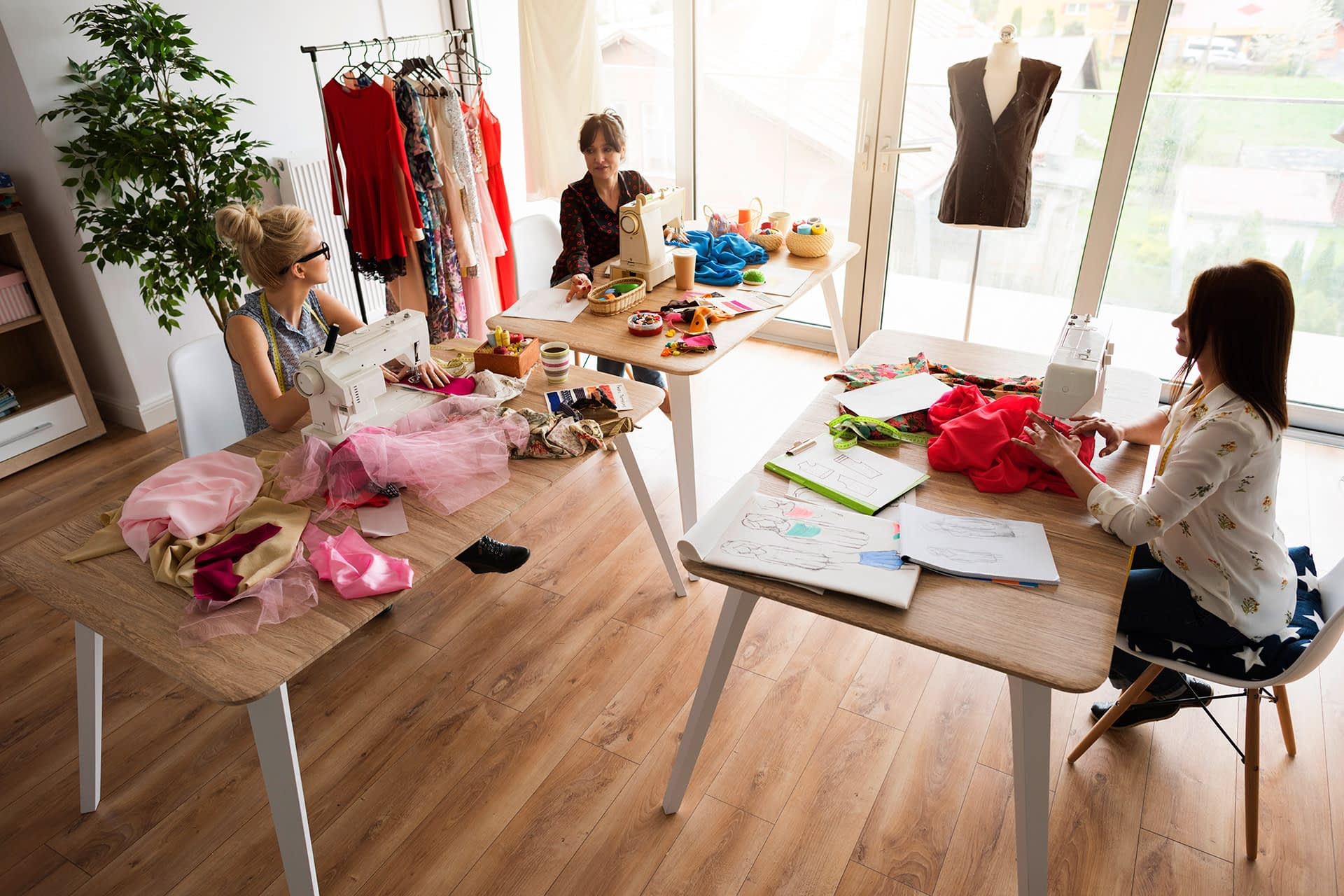 Female fashion designers are making clothes in a cozy workshop.